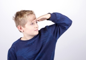 boy looking forward his hand to his head. blue-eyed. blonde in a blue sweater. Isolated on white background